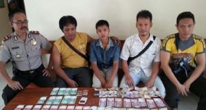 AMANKAN -- Tersangka Anton Wijaya (22) tengah diamankan Polsek Mesuji Raya Iptu Bambang Pancawala didampingi personil, karena berbelanja di warung memakai uang palsu